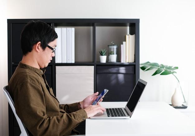 男は、コロナウイルスまたはcovid19パンデミックの家の秩序と社会的距離を保つために携帯電話とコンピューターのラップトップに取り組んでいます。