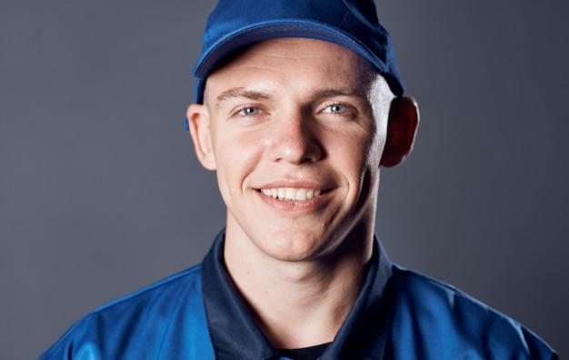Man in work uniform blue cap cropped view work service