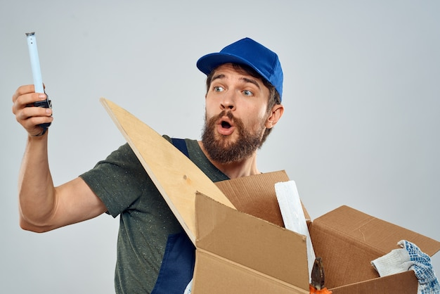 Man in work uniform with box in hands tools lifestyle light space.
