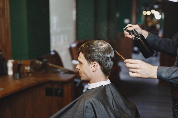 男は髪の毛で働きます。クライアントと美容師。