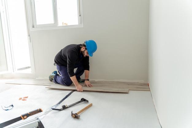 라미네이트 바닥을 조립하는 남자 노동자.