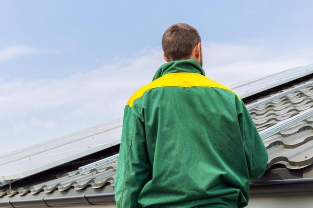 Инженер рабочего человека против станции солнечных батарей на крыше дома. вид сзади до неузнаваемости силуэт. экологическая концепция альтернативных источников энергии.