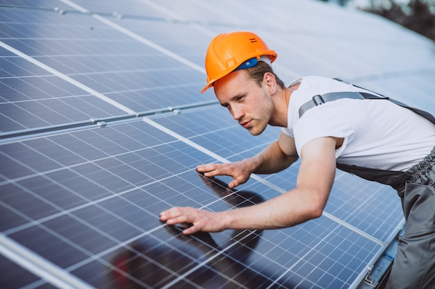 Man worker in the firld by the solar panels