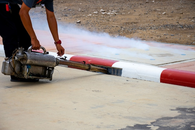 デング熱とジカウイルスを防ぐために蚊を排除するために殺虫剤を噴霧する男性労働者