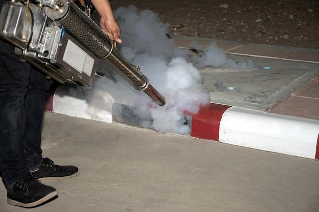 デング熱とジカウイルスを防ぐために蚊を駆除するために殺虫剤を噴霧する男性労働者