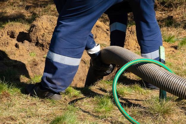 パイプを握り、屋外で下水道清掃サービスを提供する男性労働者。