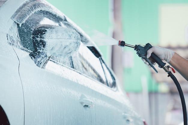 Рабочий человек в гараже с помощью инжектора пены под высоким давлением распыляет грязный белый автомобиль.