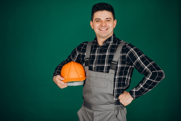 Человек работник в шляпе, изолированные на зеленой стене