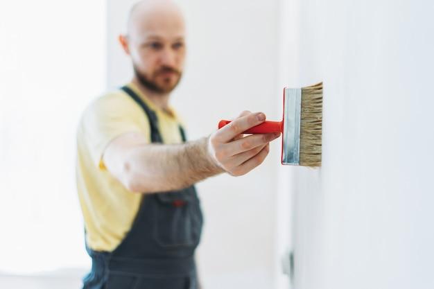 Рабочий в спецодежде ремонтирует, клеит стены под обои или грунтовку на стену выборочный фокус