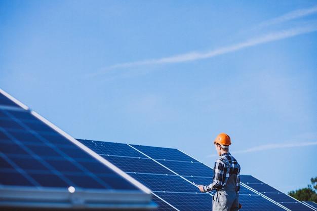 Человек рабочий в первых рядах от солнечных батарей