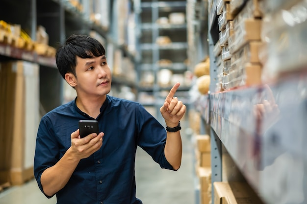 Man worker using smartphone to check inventory in the warehouse store