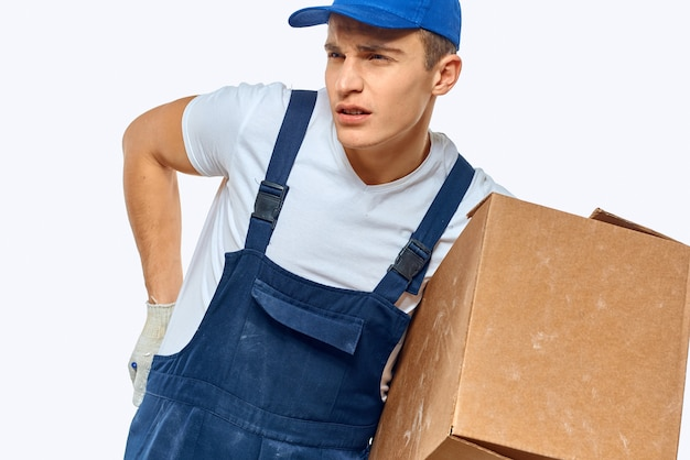 Man worker with box in hands delivery loading service work light background.