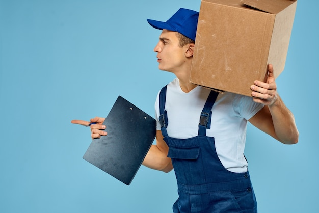 Man worker with cardboard box delivery loader lifestyle blue wall.