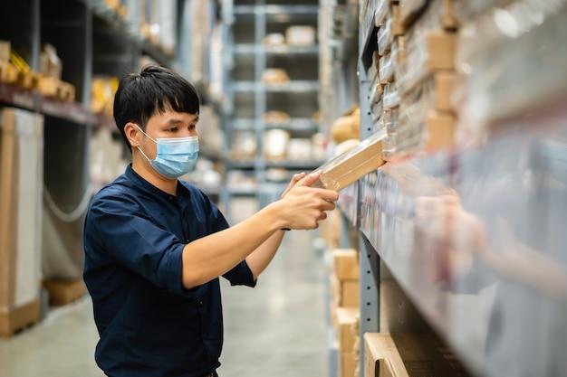 코로나 바이러스 전염병 동안 창고에서 재고를 확인하는 의료 마스크를 가진 남자 노동자