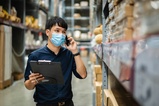 코로나 바이러스 전염병 동안 창고에서 재고를 확인하기 위해 휴대 전화로 이야기하고 클립 보드를 들고 의료 마스크를 가진 남자 노동자 프리미엄 사진