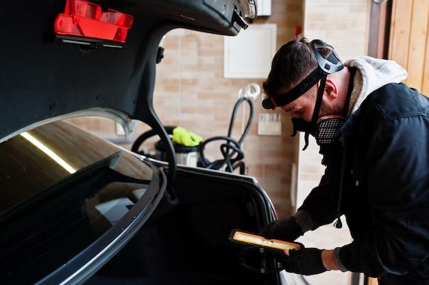 자동차 자세히에서 일하는 남자를 닫습니다.