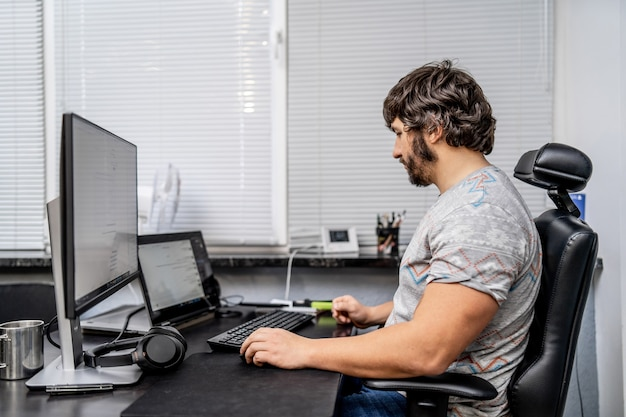 クリエイティブオフィスのデスクで働く男。