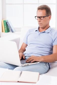 家で働く男。自宅のソファに座ってラップトップに取り組んでいる自信を持って成熟した男