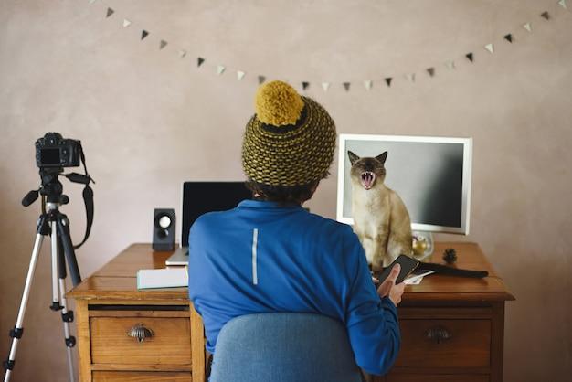 猫と一緒に在宅勤務の男性