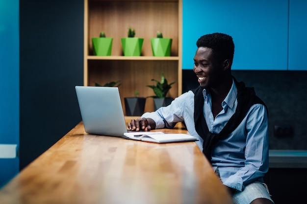 キッチンの机の上にラップトップ、在宅勤務、フリーランスのコンセプトで自宅で働く男。