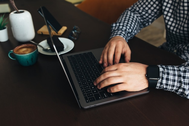 커피와 초콜릿 케이크, 전화, 식물 한잔과 함께 노트북에서 일하는 남자. 고품질 사진