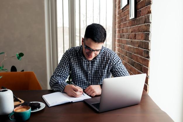 自宅でコーヒーを飲みながらノートパソコンで作業している男性。背景がぼやけている。高品質の写真
