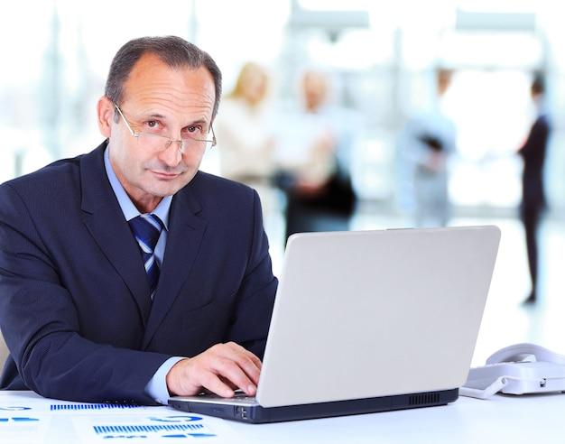 ノートパソコンでオフィスで働く男
