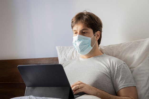 Man working in bed, doing home office because he is sick. using a mask over the mouth and nose.