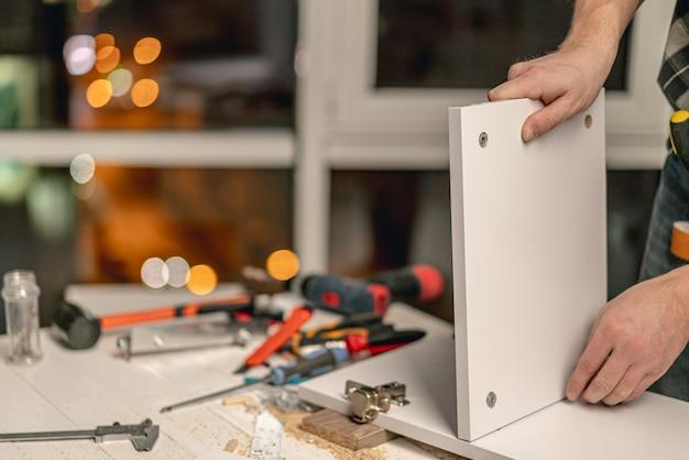 워크숍에서 목재 가구 제조 과정에서 선반의 연결 보드를 작업하는 사람