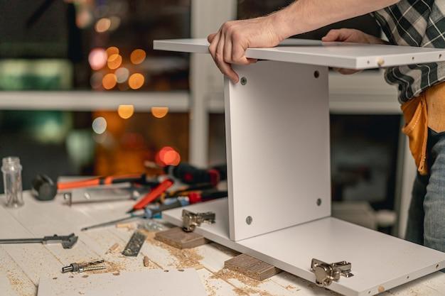 Человек работает соединительная доска полки в процессе производства деревянной мебели