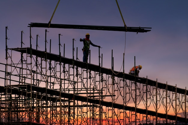 Man working on construction site with scaffold and building, scaffolding for construction factory