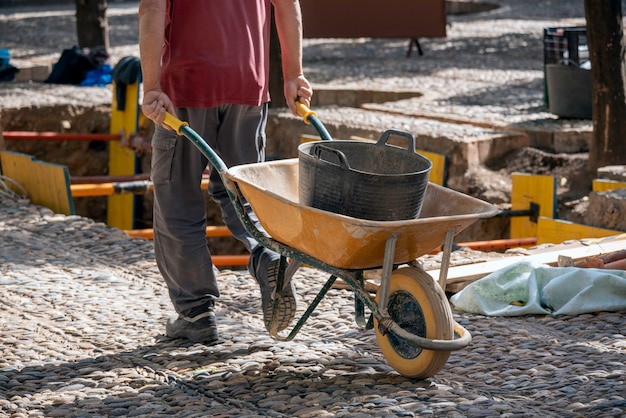 Man working in a construction with a wheelbarrow