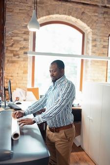 働く男。忙しい感じで出版社で働く縞模様のシャツを着た浅黒い肌の男