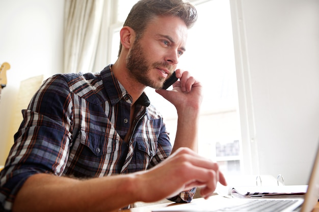 Man working at desk with cellphone and laptop