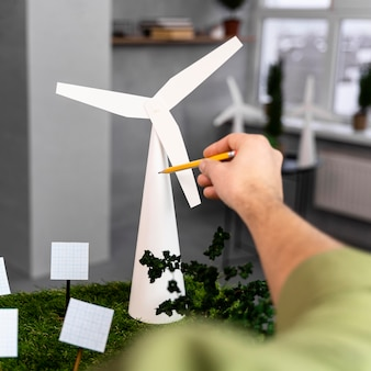 Man working on an eco-friendly wind power project layout with wind turbine