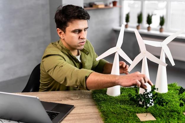 Uomo che lavora a un progetto di energia eolica ecologico con turbine eoliche