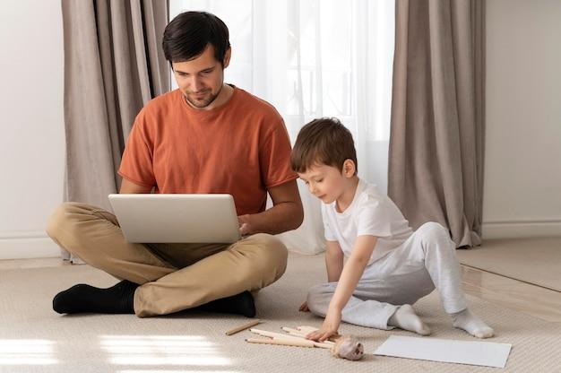 Uomo che lavora sul pavimento con il figlio pieno colpo