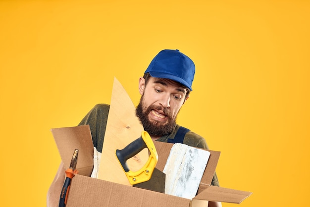 A man in a working form a box with loading tools yellow wall.