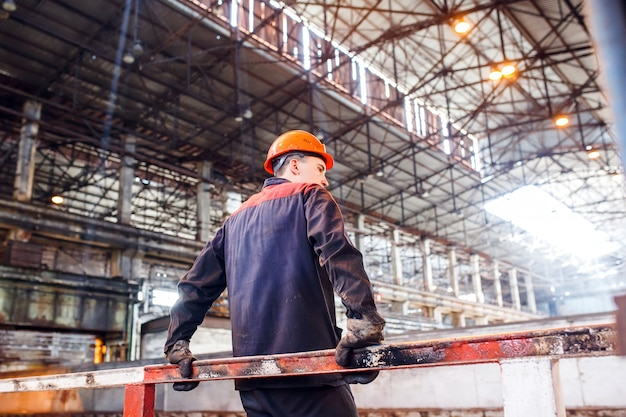 A man in a working form on a metallurgical plant. tired of work worker.