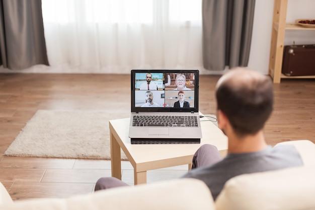 検疫中に彼のチームとのビデオ通話で自宅で働いている男性。