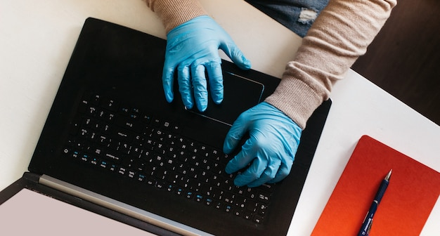 A man working from home on a laptop wearing disposable gloves for protection. coronavirus outbreak. quarantined business man. work at home. stay at home.