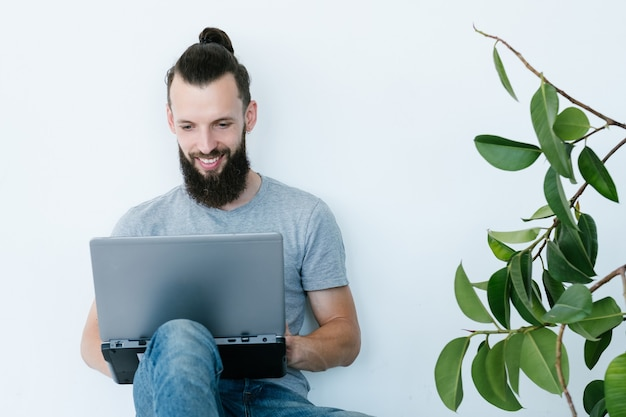 在宅勤務の男性。インターネットでお金を稼ぐ。ラップトップを保持している若いひげを生やしたヒップスター。フリーランスの仕事とリモートワークの概念。