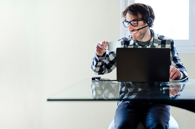 インターネットサーフィンをしている机に座っているラップトップコンピューターで自宅で働いている男