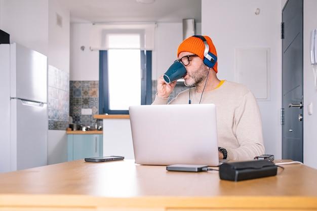 인터넷을 서핑하고 커피를 마시는 책상에 앉아 노트북으로 집에서 일하는 사람