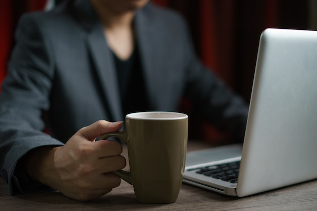 컴퓨터를 사용 하 고 차 한잔 마시는 가정에서 일하는 남자