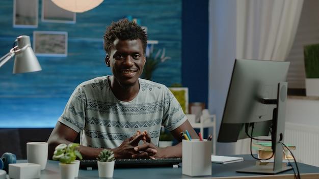 コンピューターとキーボードを使用して自宅で仕事をしている男性