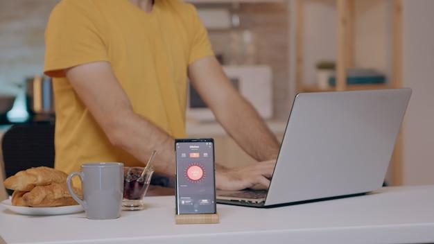 スマートフォンで制御された音声を使用して照明をオンにする自動照明システムを使用して自宅で作業している男性。スマートスピーカーガジェットはコマンドに応答し、電気効率を制御する人