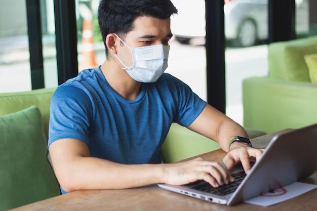 Человек работает из дома с ноутбуком и носить маску
