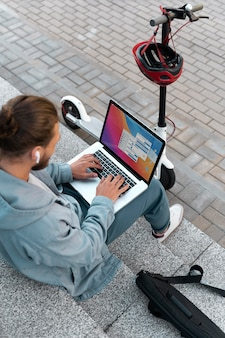 Man working on his laptop next to his scooter