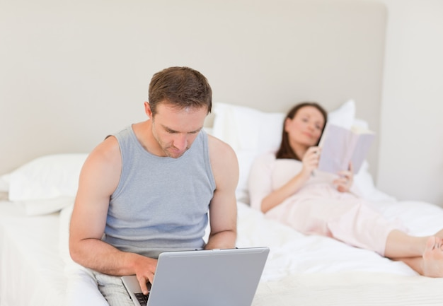 Man working on his laptop while his wife is reading a book on the bed